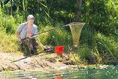 使用网的渔夫登陆鱼 免版税库存图片