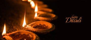 使用美丽的黏土diya灯的愉快的屠妖节贺卡设计在diwali夜庆祝点燃了 印地安印度轻的节日加州 库存图片