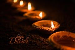使用美丽的黏土diya灯的愉快的屠妖节贺卡设计在diwali夜庆祝点燃了 印地安印度轻的节日加州 图库摄影