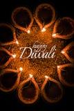 使用美丽的黏土diya灯的愉快的屠妖节贺卡设计在diwali夜庆祝点燃了 印地安印度轻的节日加州 免版税库存照片