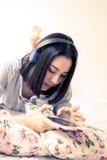 使用耳机和手机,女孩听 免版税库存照片