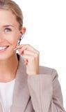使用耳机的一名微笑的女实业家的特写镜头 库存图片