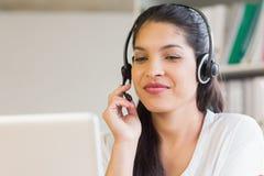 使用耳机的女实业家在办公室 免版税库存照片