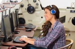 使用耳机的少妇和研究计算机 免版税库存图片