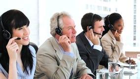使用耳机的愉快的企业队 免版税图库摄影