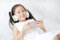 使用耳机的愉快的矮小的亚裔女孩由智能手机听音乐微笑和看照相机的,当在家时说谎在床上 免版税库存照片