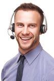 使用耳机的英俊的微笑的年轻商人 免版税库存照片