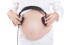 使用耳机,体贴的孕妇给未出生的孩子听到音乐 免版税图库摄影