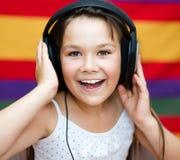 使用耳机,女孩享受音乐 免版税库存图片
