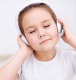 使用耳机,小女孩享受音乐 免版税图库摄影