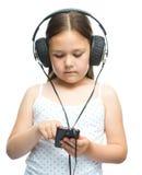 使用耳机,小女孩享受音乐 库存图片