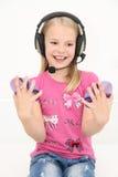 使用耳机,逗人喜爱的小女孩享受音乐 免版税库存照片