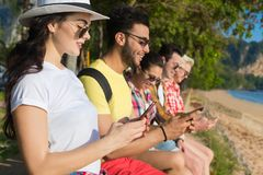 使用聊天网上假日海暑假的细胞巧妙的电话热带公园棕榈树朋友的青年人小组 免版税库存图片
