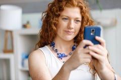使用聪明电话微笑的愉快的美丽的年轻女实业家 免版税图库摄影
