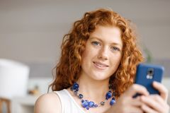 使用聪明电话微笑的愉快的美丽的年轻女实业家 免版税库存照片