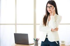 使用聪明电话谈话的亚裔可爱的女实业家 库存照片