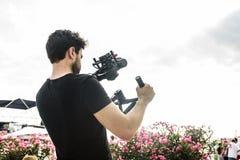 使用肩膀steadicam,摄影师拍摄录影在照相机 库存图片
