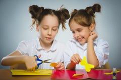 使用胶浆和剪刀,女孩做某事从色纸 图库摄影