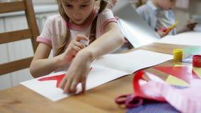 使用胶浆棍子的女孩为做她的假日装饰的应用心脏与兄弟在背景 股票视频