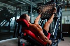 使用腿的性感的肌肉人按机器和安置他的腿在黑暗的五颜六色的背景的平台 免版税库存照片