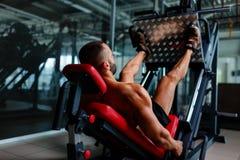 使用腿的性感的肌肉人按机器和安置他的腿在黑暗的五颜六色的背景的平台 免版税库存图片