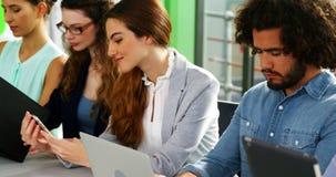 使用膝上型计算机、手机和数字式片剂的商业主管在会议 影视素材