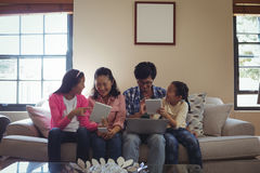使用膝上型计算机、数字式片剂和手机的家庭在客厅 免版税库存照片
