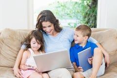 使用膝上型计算机、数字式片剂和手机的家庭 免版税图库摄影