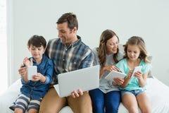 使用膝上型计算机、数字式片剂和手机的微笑的家庭在卧室 免版税库存图片