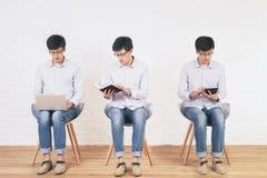 使用膝上型计算机、片剂和读书 免版税图库摄影