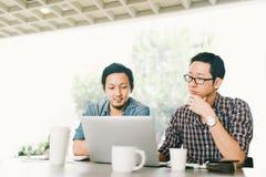 使用膝上型计算机、起始的项目会议或者配合突发的灵感,英俊的亚裔企业同事或大学生  库存图片