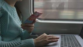 使用膝上型计算机个人计算机和智能手机触感衰减器的女性手在火车 笔记本少妇感人的触摸屏幕的胳膊  股票视频