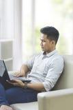 使用膝上型计算机个人计算机的年轻人,当在家时坐长沙发 免版税库存图片
