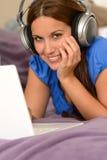 使用有耳机的年轻微笑的女孩膝上型计算机 库存照片