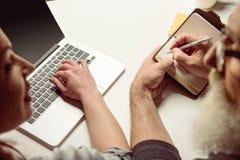 使用膝上型计算机和人的妇女做笔记 免版税库存照片