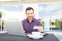 使用膝上型计算机和信用卡的人在商城 免版税库存照片