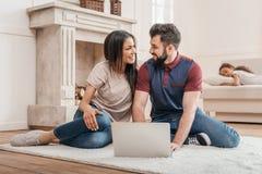 使用膝上型计算机和在家微笑的不同种族的夫妇 免版税库存照片