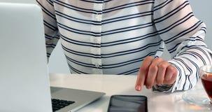 使用膝上型计算机和手机在桌4k上的妇女 股票录像