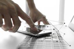 使用膝上型计算机和手机的商人手 免版税库存照片