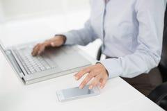 使用膝上型计算机和手机的女实业家的侧视图中间部分 免版税图库摄影