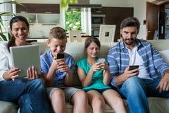 使用膝上型计算机和手机的家庭在客厅 库存图片