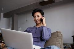 使用膝上型计算机和手机的英俊的快乐亚裔人 免版税图库摄影