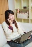 使用膝上型计算机和手机的年轻亚裔妇女 免版税库存照片