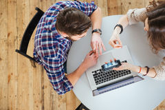 使用膝上型计算机和手机,结合坐在圆桌上 库存图片