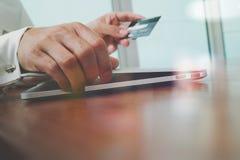 使用膝上型计算机和拿着信用卡的手与安全付款 图库摄影