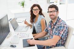 使用膝上型计算机和数字化器的微笑的商人 库存图片