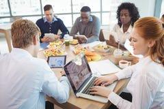 使用膝上型计算机和数字式片剂的企业同事在早餐桌附近 库存图片
