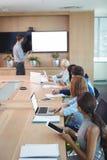使用膝上型计算机和数字式片剂的商人在会议桌在会议期间 图库摄影