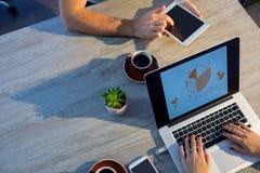 使用膝上型计算机和数字式片剂的董事在会议期间 库存图片