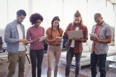 使用膝上型计算机和数字式片剂的年轻创造性的商人在办公室 免版税图库摄影